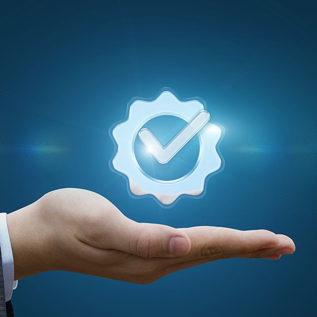 A hand holding a icon of a gear with a checkmark in the center