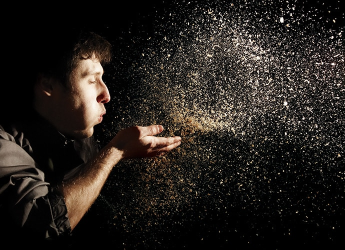 A man is blowing dust on his hand