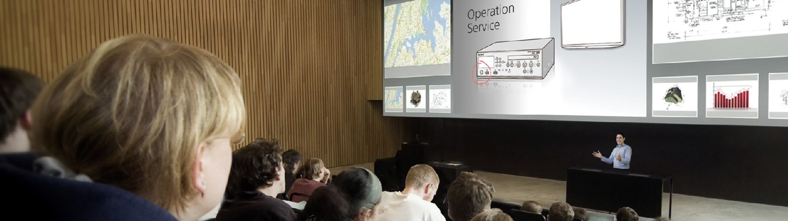 A presenter introducing 'Operation Service' to audience in a conference hall