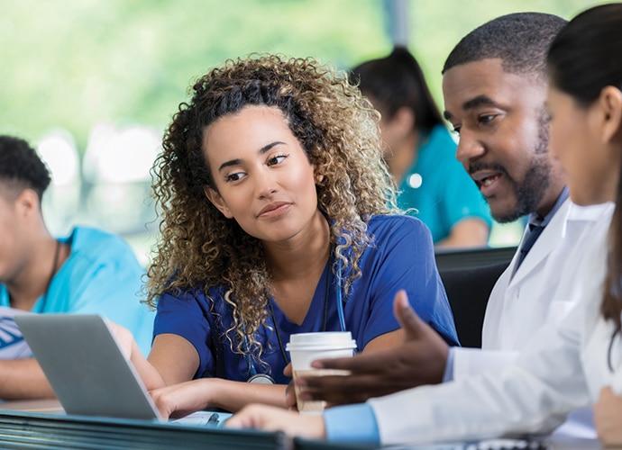 Medizinstudierende und Ärzte tauschen sich in einem Unterrichtsraum aus
