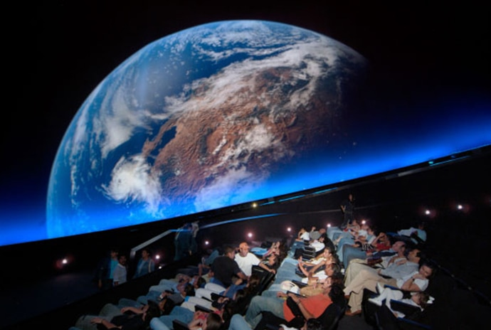 An image of earth on a planetarium screen with an audience watching.