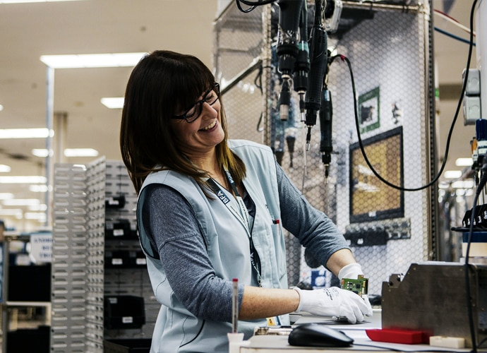 Image from within a Sony repair centre, showing a smile engineer working on a product.