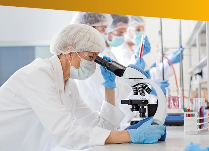 Technik laboratoryjny patrzący przez mikroskop wlaboratorium