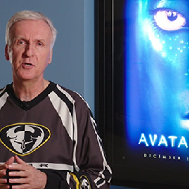 A portrait of film director James Cameron in front of an illuminated poster of the film Avatar.