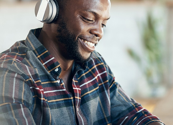 A man smiling and wearing headphones as he works from home