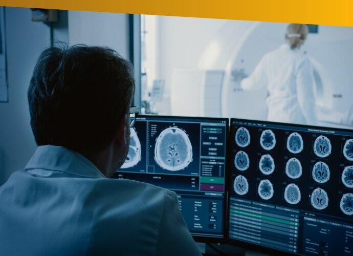 Mężczyzna wfartuchu laboratoryjnym patrzący na ekran cyfrowy
