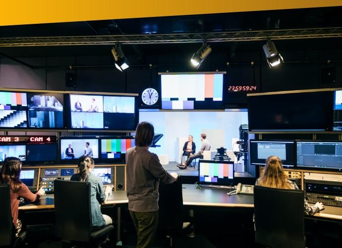 3kobiety siedzące przed monitorami na biurku istojąca za nimi kobieta zwrócona wstronę monitora
