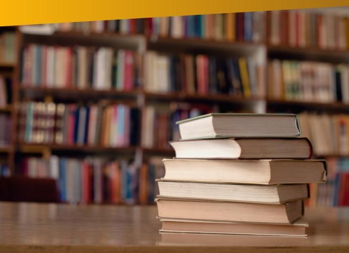 Stos książek na stole iregały zksiążkami wtle