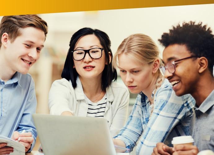 2studentki i2studentów siedzących, patrzących na ekran laptopa iśmiejących się