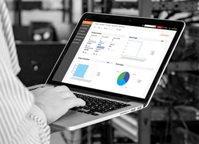 Une personne utilise un ordinateur portable pour visualiser des données sur son lieu de travail, toutes les informations étant pilotées par TEOS.