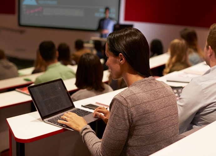Woman on laptop in lecture hall