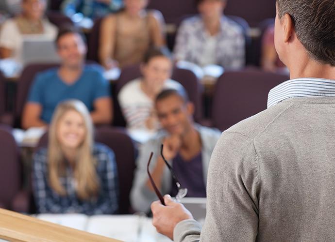Hombre parado al frente de un auditorio, realizando una presentación ante estudiantes de educación superior