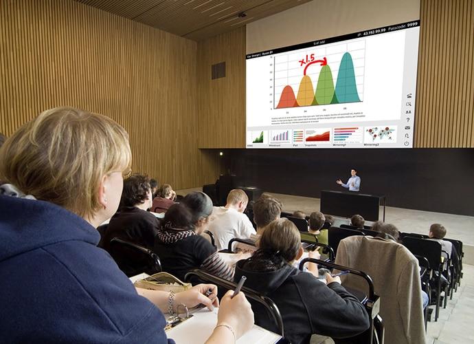 Großer Vorlesungssaal mit Studierenden, die sich eine Präsentation ansehen