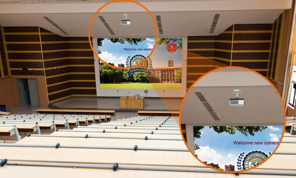 View from the back of a lecture hall, looking towards a screen at the front of the room. A projector is mounted closely to the ceiling showing the flexibility of installation in rooms with high ceilings