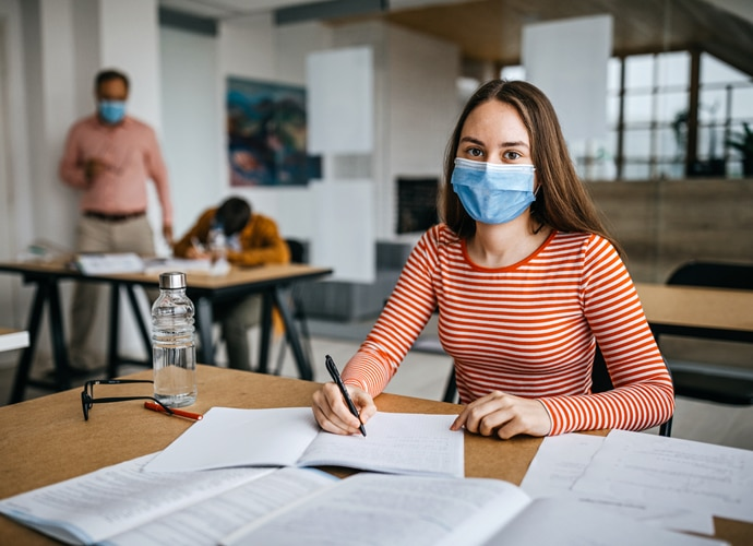 Teenage girl wearing a blue facemask in a classroom. In the background you can see another student and a teacher, both wearing masks. They are sat far apart, conforming with social distancing.