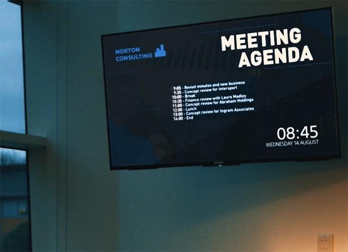 Un écran professionnel fixé au mur affichant l'ordre du jour d'une réunion.