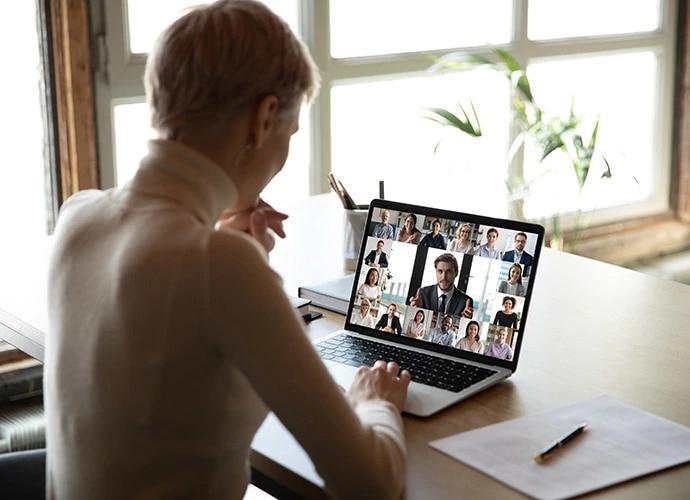 Evde dizüstü bilgisayarının başında oturmuş bir kadın görüntülü konferansa katılıyor.