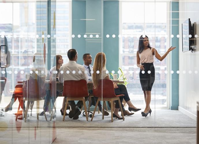 Une femme fait une présentation dans une petite salle de réunion moderne.