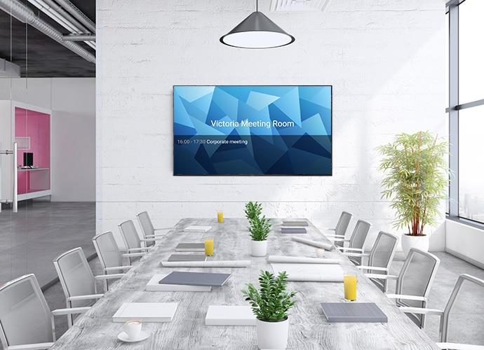 Duvara monte edilmiş BRAVIA Profesyonel Ekranın bulunduğu aydınlık, modern bir toplantı odasının görüntüsü.