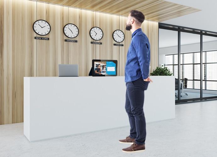 Ein Mann steht an einem Empfangstresen. Auf dem Schreibtisch befindet sich ein Tablet mit TEOS, wodurch er ohne fremde Hilfe einchecken kann.