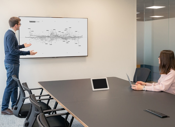 Image showing a man stood presenting content on a BRAVIA Professional Display in a meeting room. A woman is watching him present.