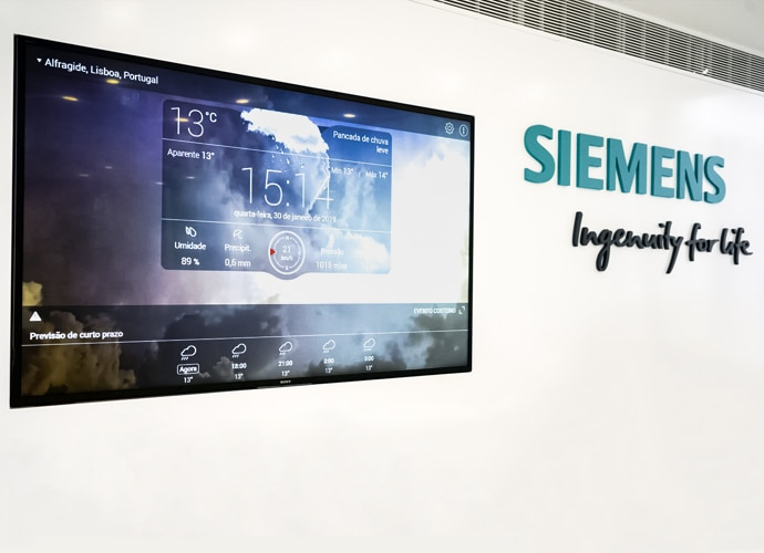 Photo from the Siemens Portugal TEOS installation, showing a wall-mounted BRAVIA Professional Display being used for digital signage. The Siemens logo is visible on the wall.