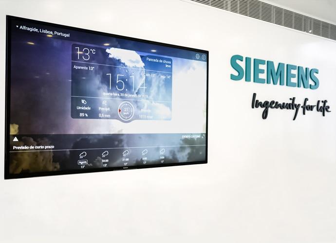 Photo de l'installation de TEOS de Siemens Portugal montrant un écran professionnel BRAVIA fixé au mur utilisé pour l'affichage dynamique. Le logo Siemens est visible sur le mur.
