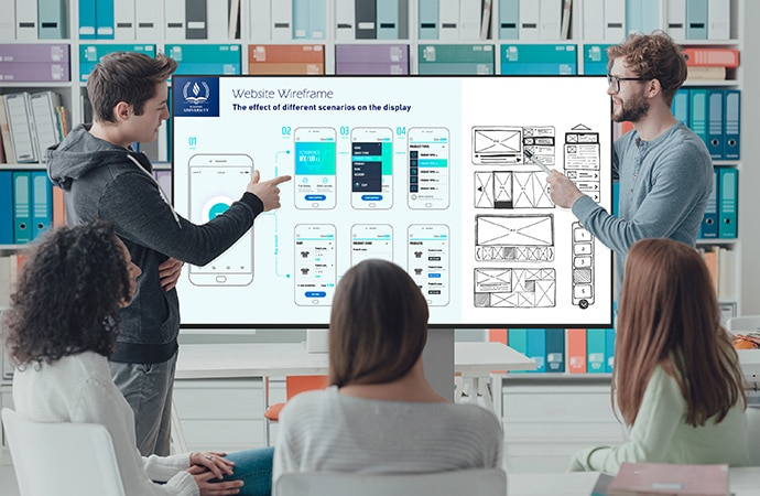 Two students present their work to their classmates on a BRAVIA screen