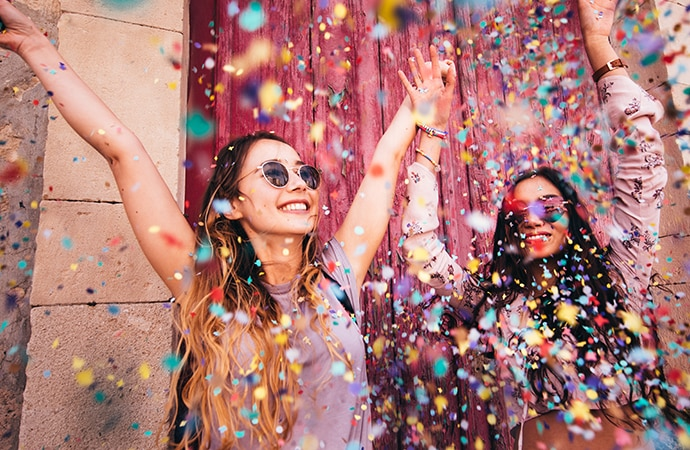 Two girls with their hands raised under confetti