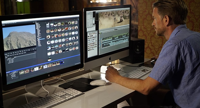 Virtual production operator watches multiple video screens