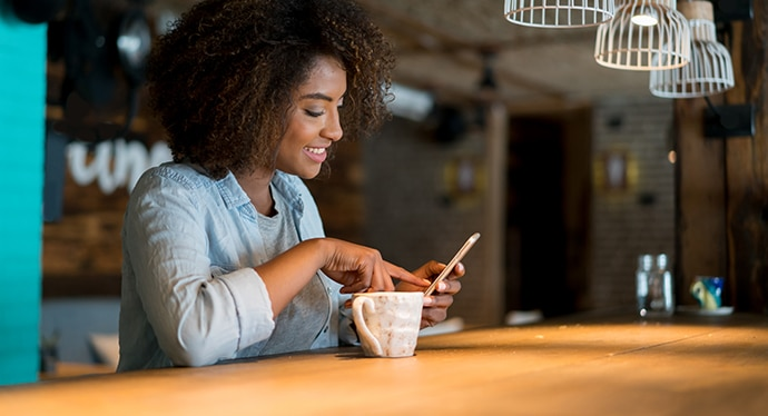 A young woman, sitting at a table, looking at her mobile device, with a cup of tea, smiling.