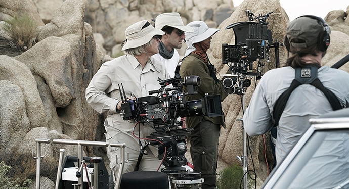 A camera crew, outside in the desert environment, filming.