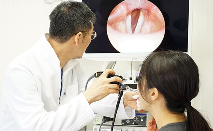 Daigo Komazawa with a patients viewing the image of a vocal cord on a Sony monitor
