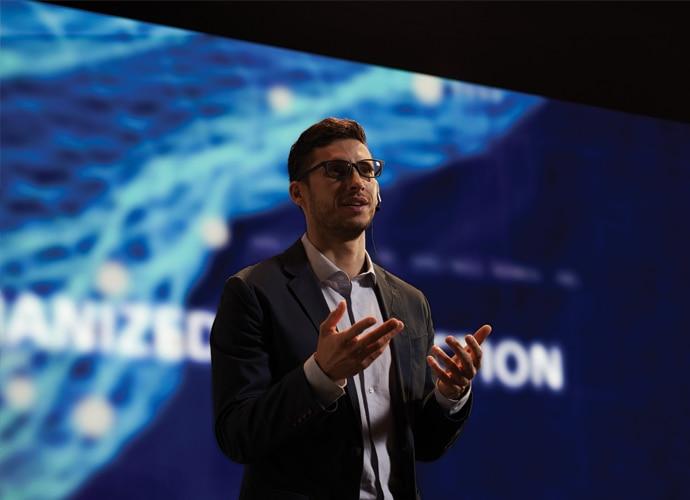 Изображение мужчины, выступающего с презентацией перед аудиторией в корпоративной среде