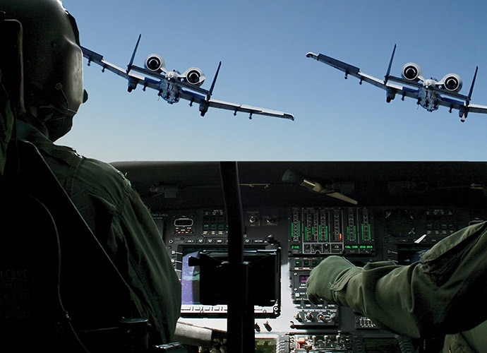 Two pilots in a military flight simulator.