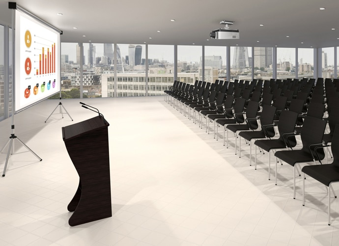 Empty presentation space, with rows of chairs facing towards a podium and a projected screen depicting business data.