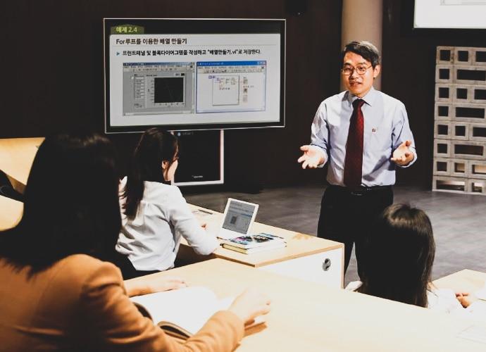 Profesor de la Cyber University of Korea dando una presentación frente a la pantalla