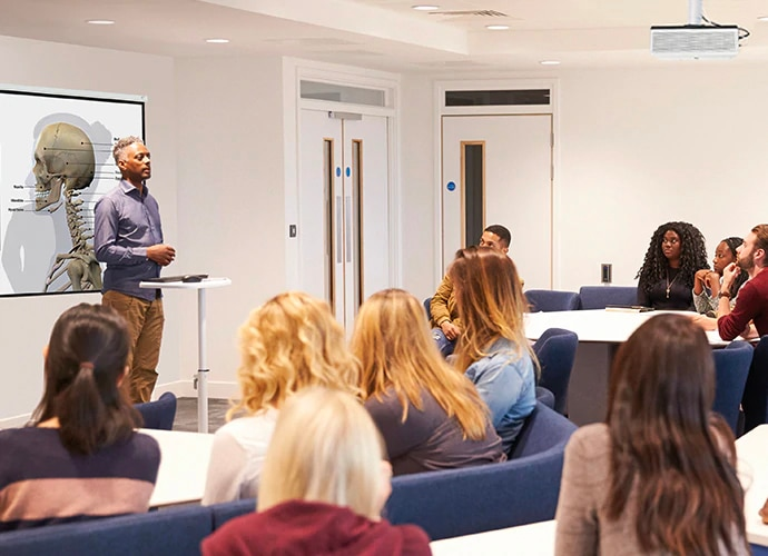 Side view of a classroom with students listening to male lecturer at the front of the class. He is stood in front of a screen which is being projected by a ceiling-mounted laser projector