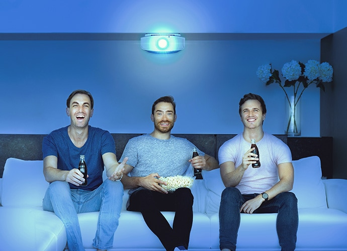 Three men sit on a sofa while watching a movie on their home cinema projector. They're drinking coke and smiling.