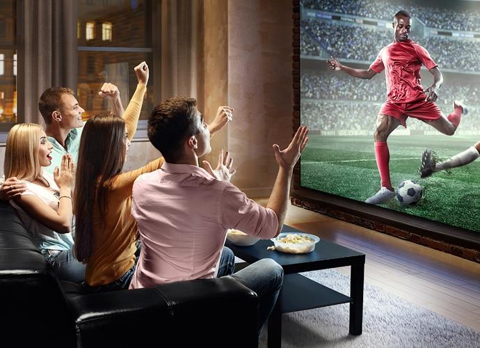 Eine Gruppe von Freunden, die sich ein Fußballspiel auf ihrer Heimkinoinstallation ansehen und jubeln.
