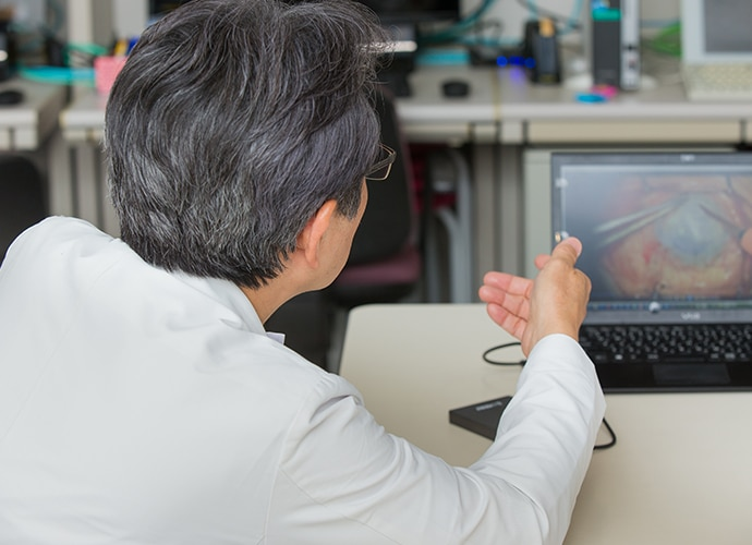 Dr Hiroshi Takahashi reviewing the recording of a surgery on a laptop