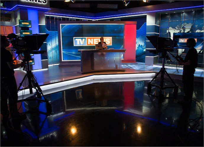 a news studio with a news reporter at the desk