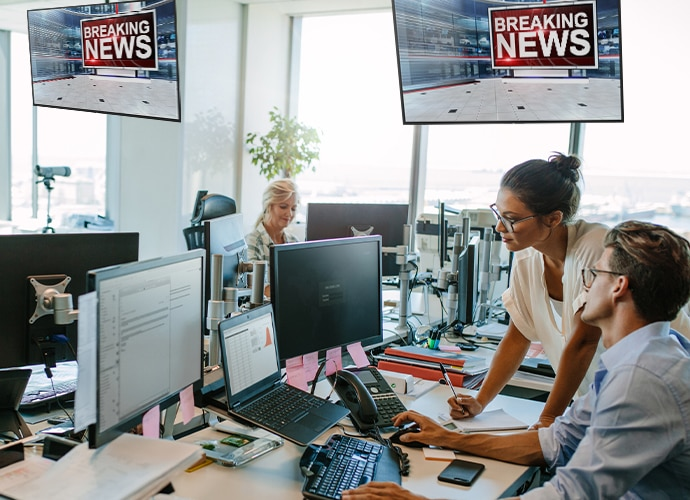a news room environment with people working around desks and bravias with breaking news above them