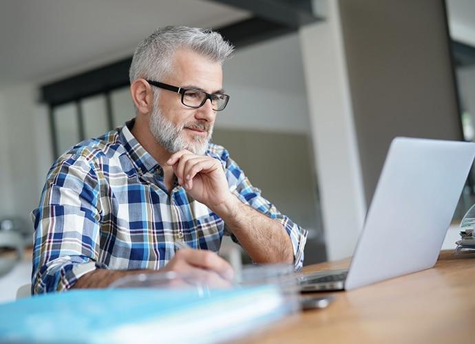 Man sitting at desk looking at laptop screen.