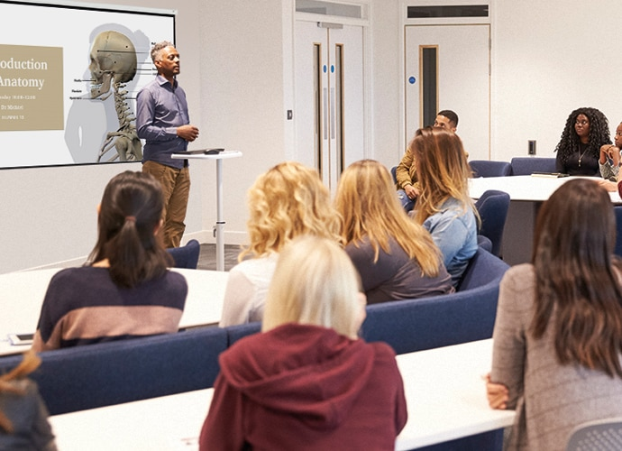 A lecturer standing in front of a full classroom