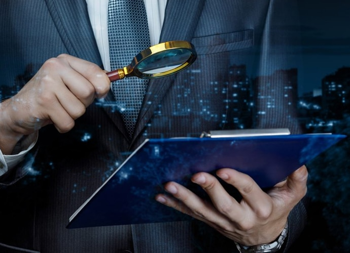 Man in business suit using a magnifying glass to look at a clipboard with some documents.