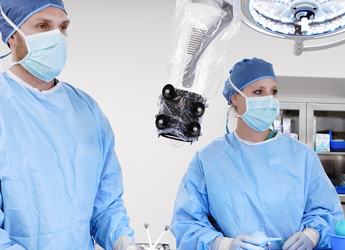 Two surgeons conducting a heads up surgery using a robotic digital microscope