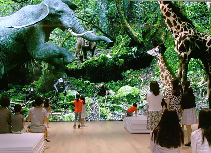 People looking at a Crystal LED wall showing wild animals.