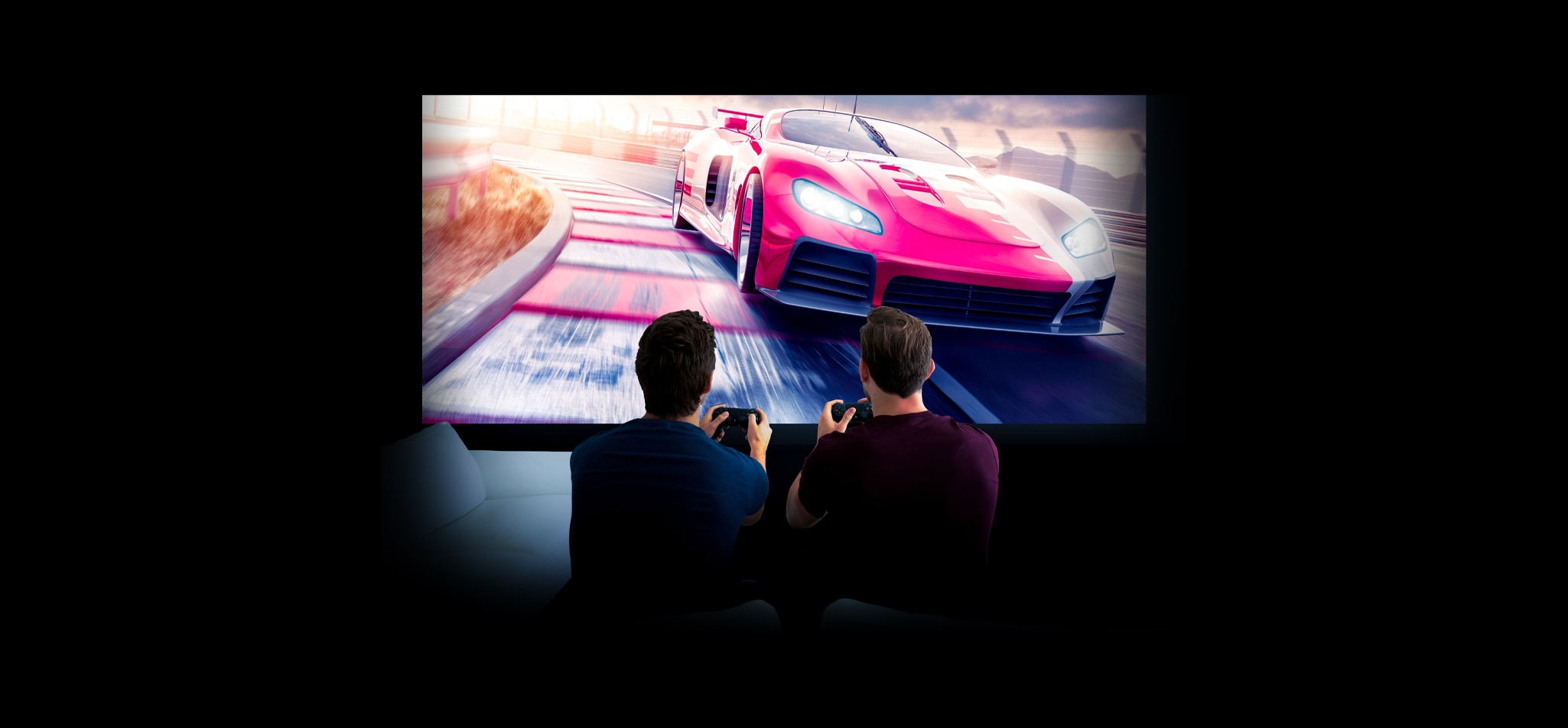 Two men are playing a video game in a home cinema. A racing car is visible on the display.