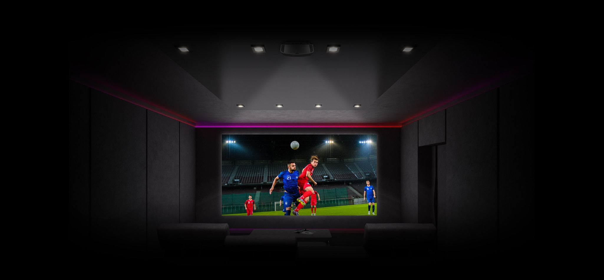 Image showing a home cinema with a projector showing a game of football. The stadium is empty due to social distancing rules.